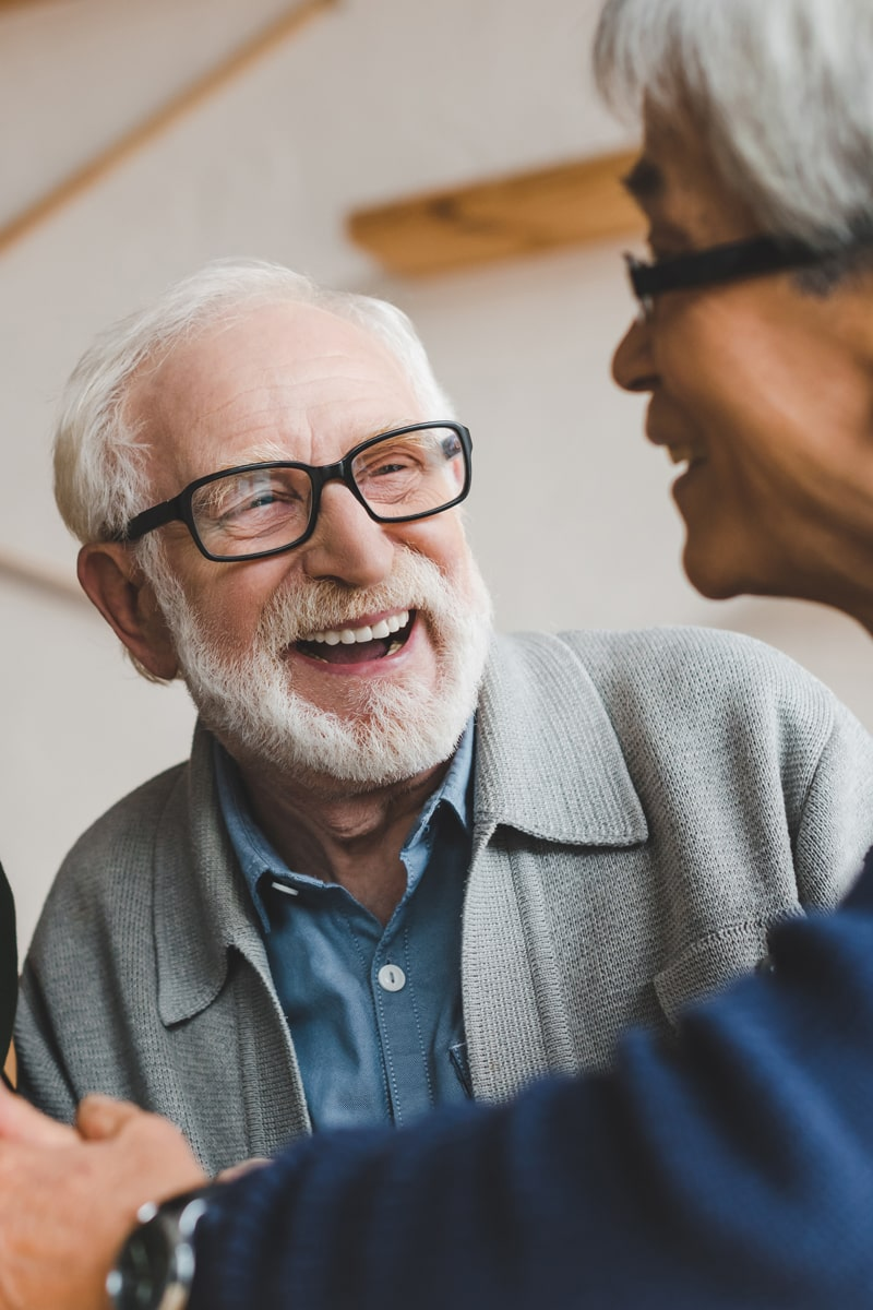 Elderly man smiling and laughing with his friend.
